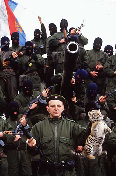 """Željko Ražnatović, przywódca paramilitarnej grupy """"Tygrysy Arkana"""", stoi przed swoimi żołnierzami w kominiarkach i z bronią. Ražnatović w jednej ręce trzyma pistolet, w drugiej małego tygrysa"""